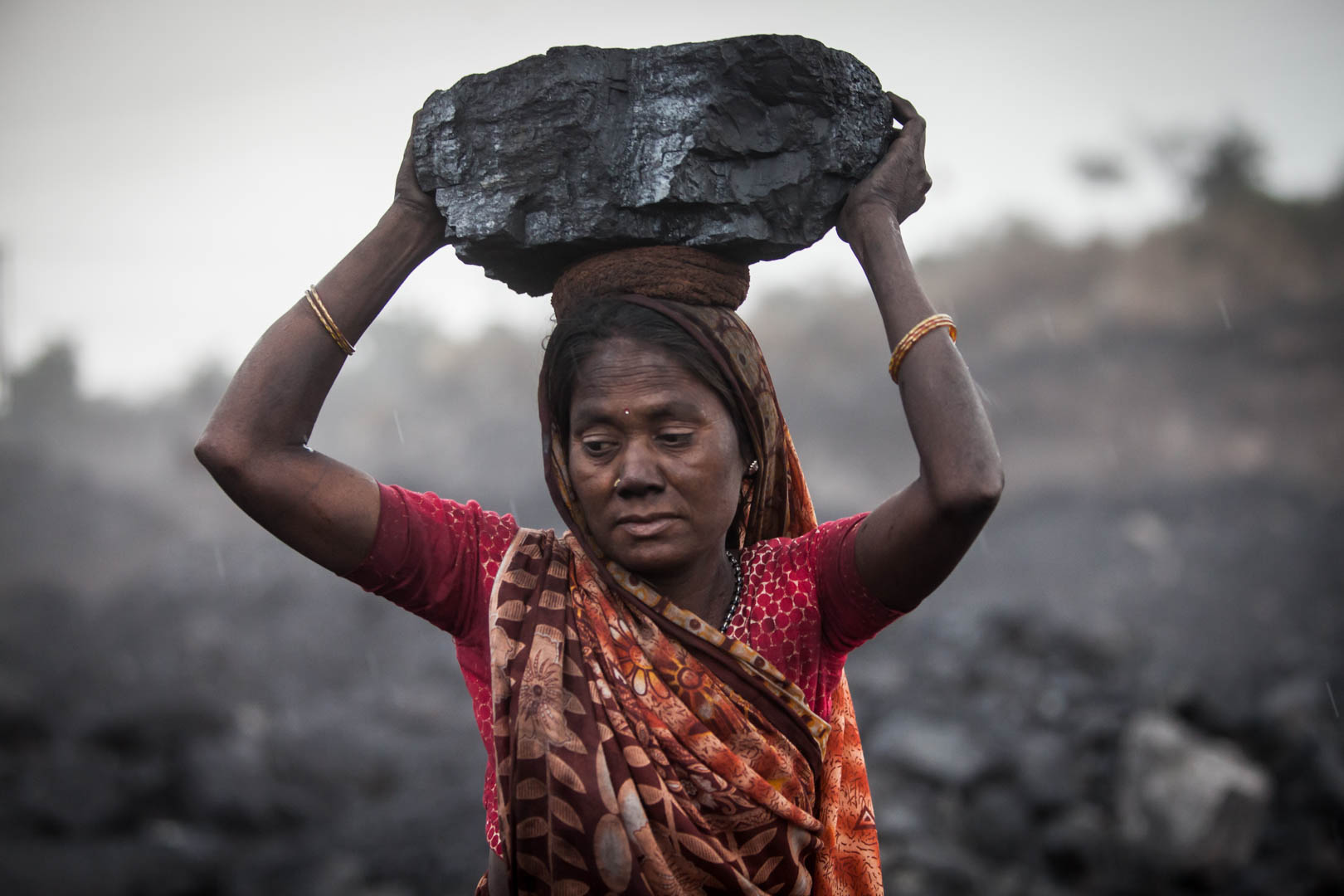 A woman is carrying a heavy chunk of coal on her head that she has collected from a government mine.