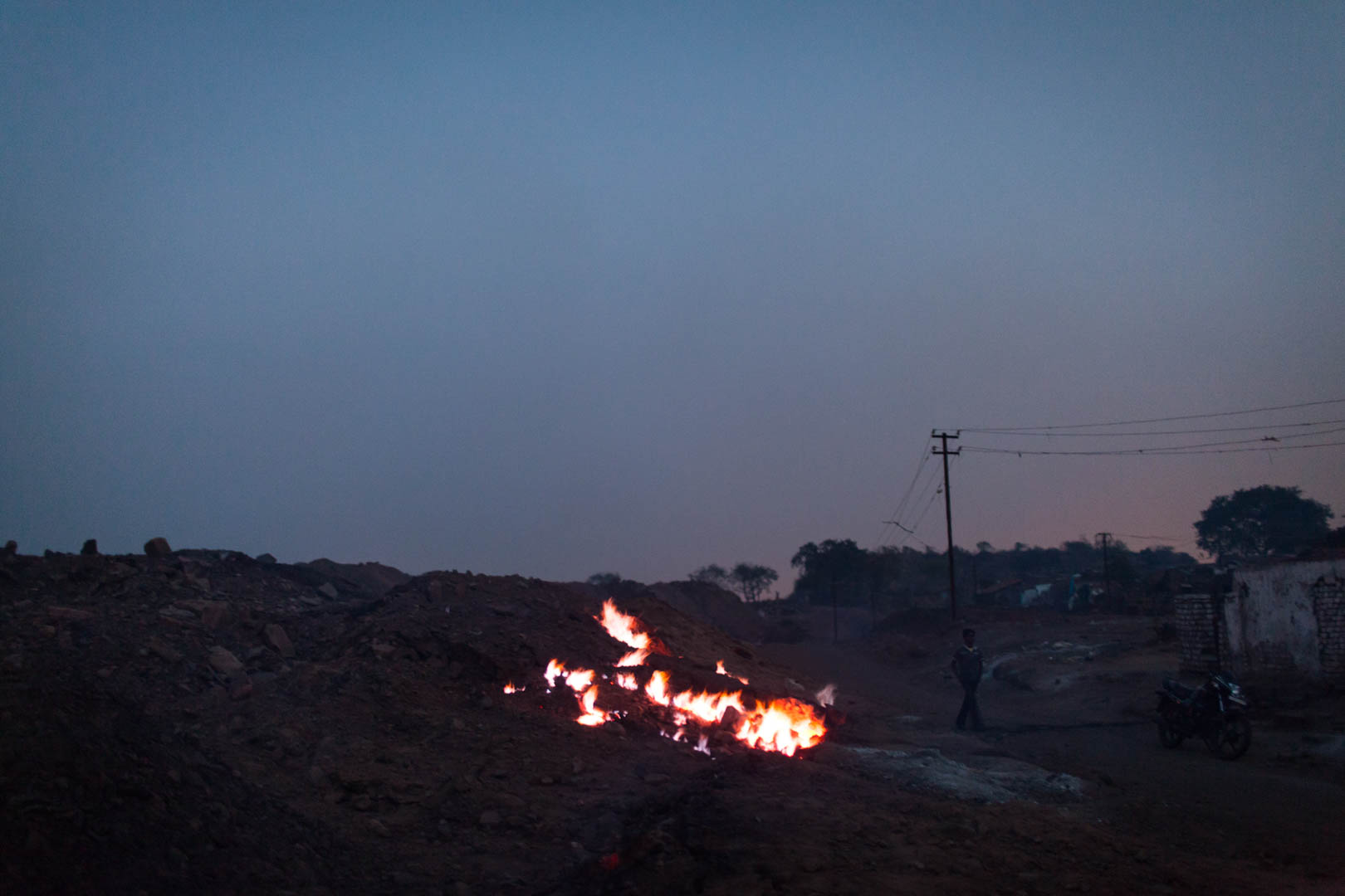 A coal-fire burns at dusk near a mine in Dhanbad.