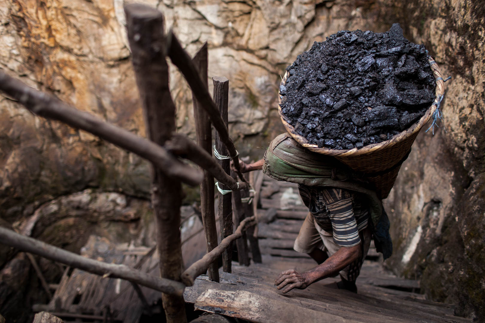 In the north-eastern state of Meghalaya, a different kind of illegal coal-mining has flourished: Because of total absence of police or authorities, business men set up underground mines in order to exploit the ground for coal. This man is carrying around 70 kilos or coal around 30 meters to the surface.