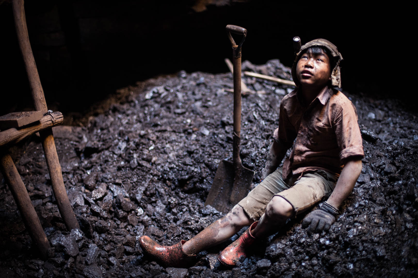 A boy from Nepal takes a break in an deep-shaft mine. His only protection equipment in the mines is a cap, gloves and rubber boots.