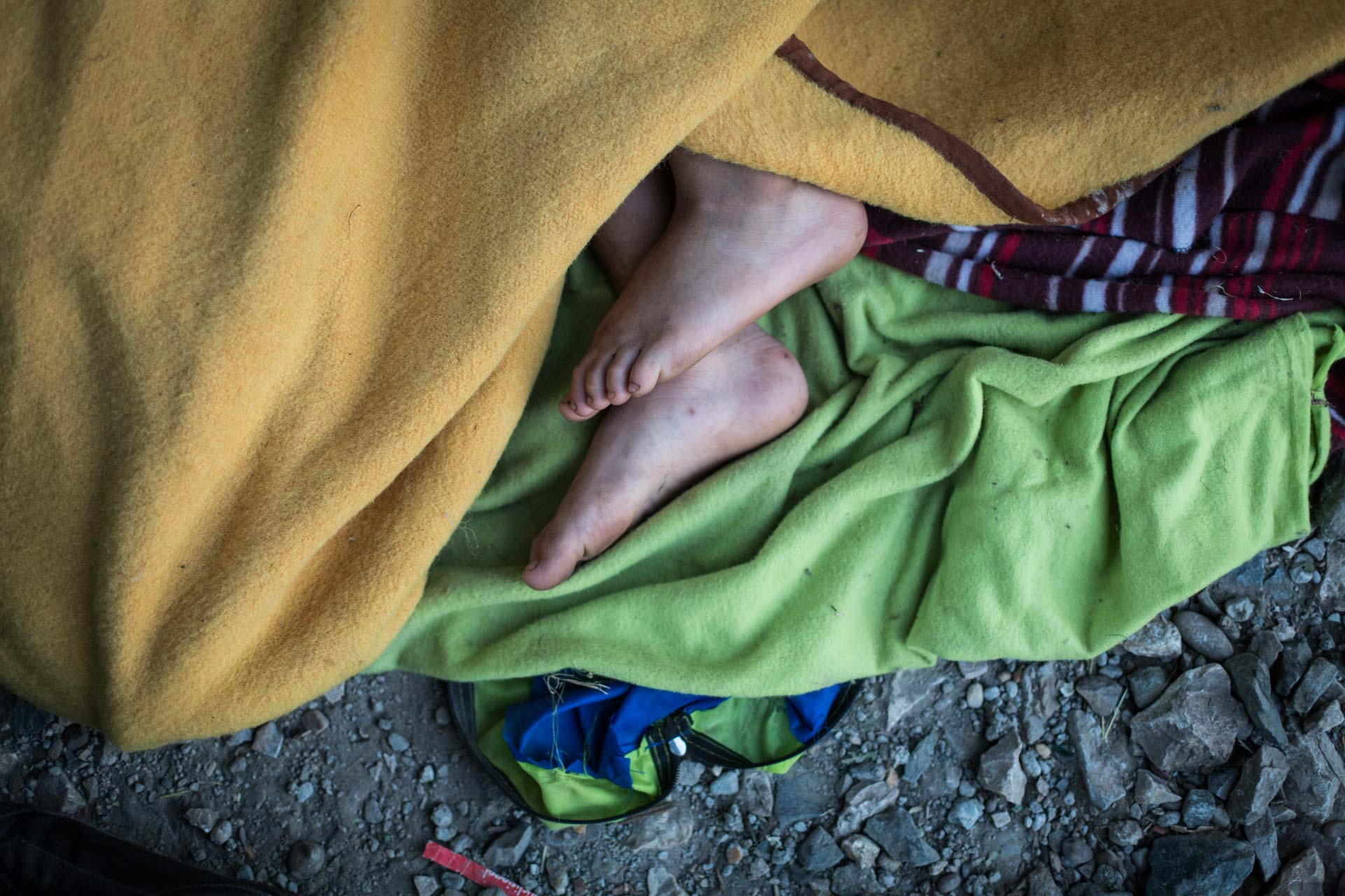 The feet of a boy are showing from beneath a blanket in the morning after spending the night in Tovarnik, Croatia.
