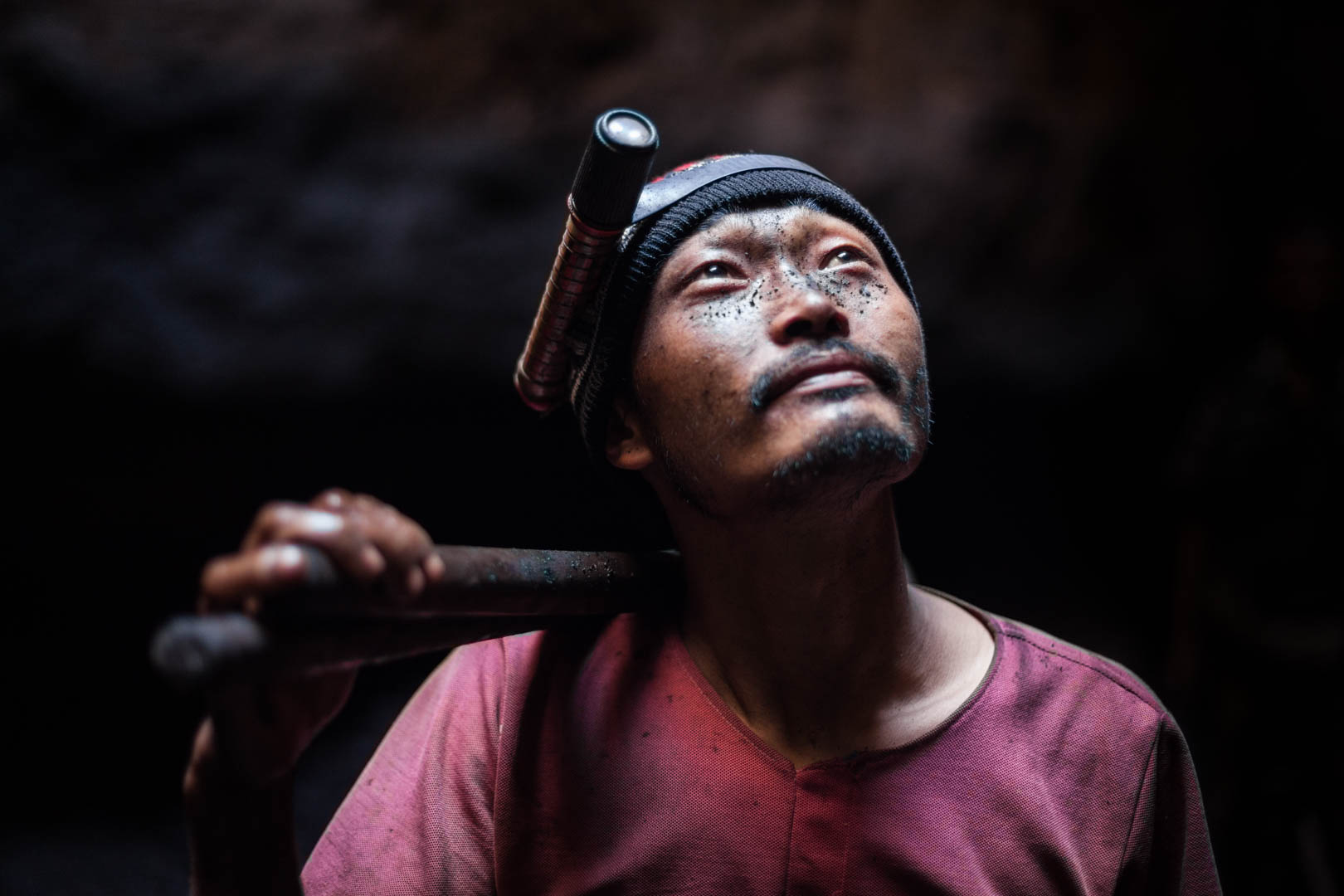 A guest worker from Bhutan looks to the surface in a mine that is about 40 meters deep.