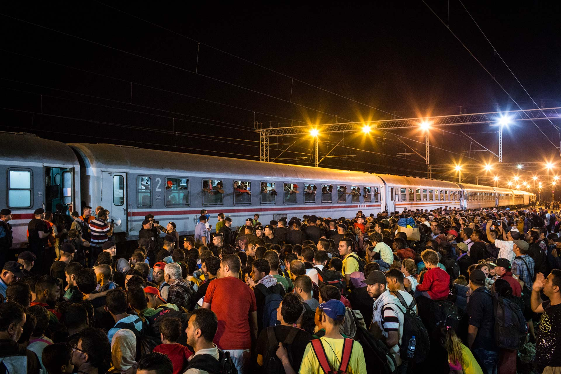Thousands of people wait for Croatian police to put them on one of the very few trains to Slovenia.