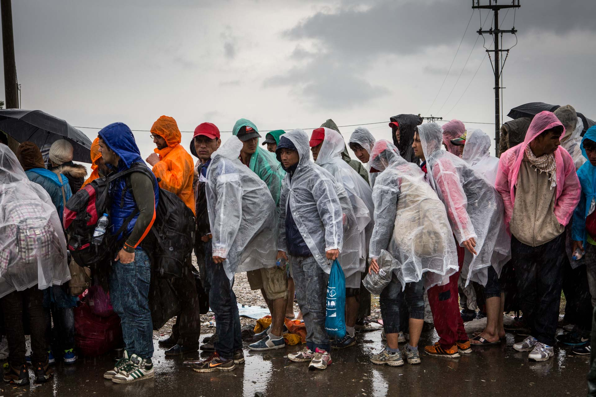 Refugees queue up for a place on a bus to Slovenia, while a rainstorm sets in in Tovarnik, Croatia.