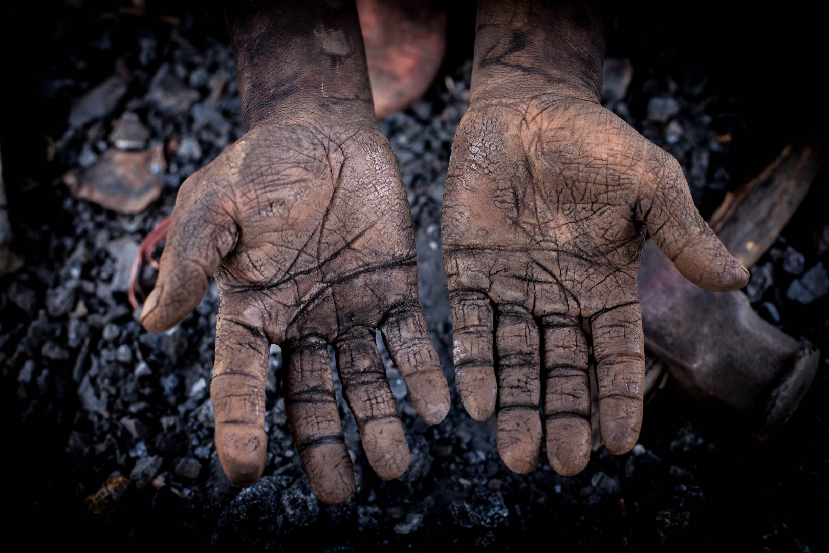 The hands of a coal miner at the end of his shift. They look like the varnish of an old oil painting.