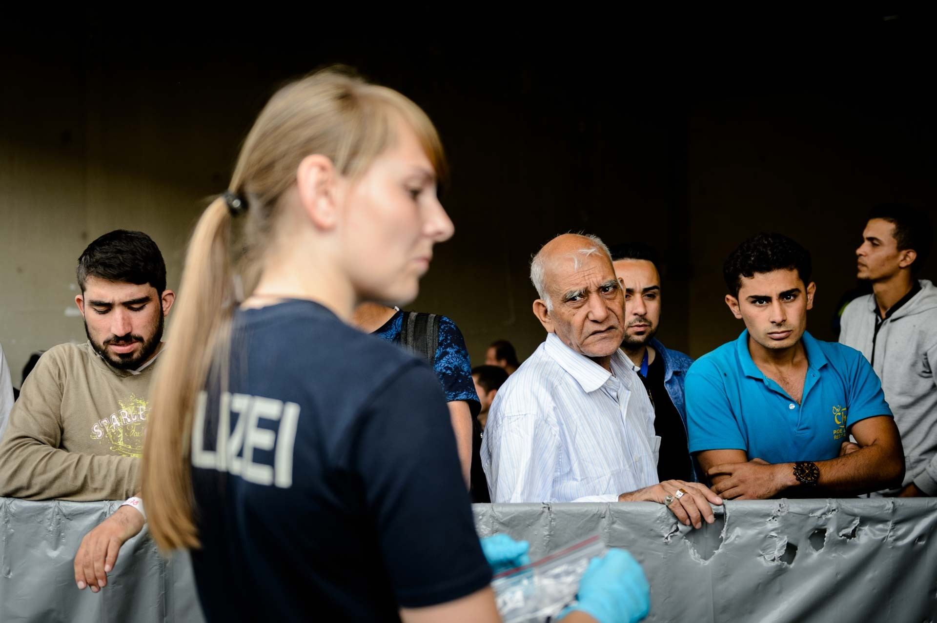 Refugees that recently arrived to Passau, a small border town in Germany, wait for their re-transfer to a processing center, where they can officially apply for asylum.