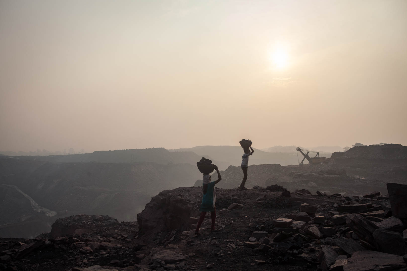 Two people carry coal that they have illegally collected in an open-cast mine run by the government around Dhanbad, shortly after sunrise. These people pay money to the guards of the mines to look away for a few hours, so that they can steal some coal to resell it on the streets.