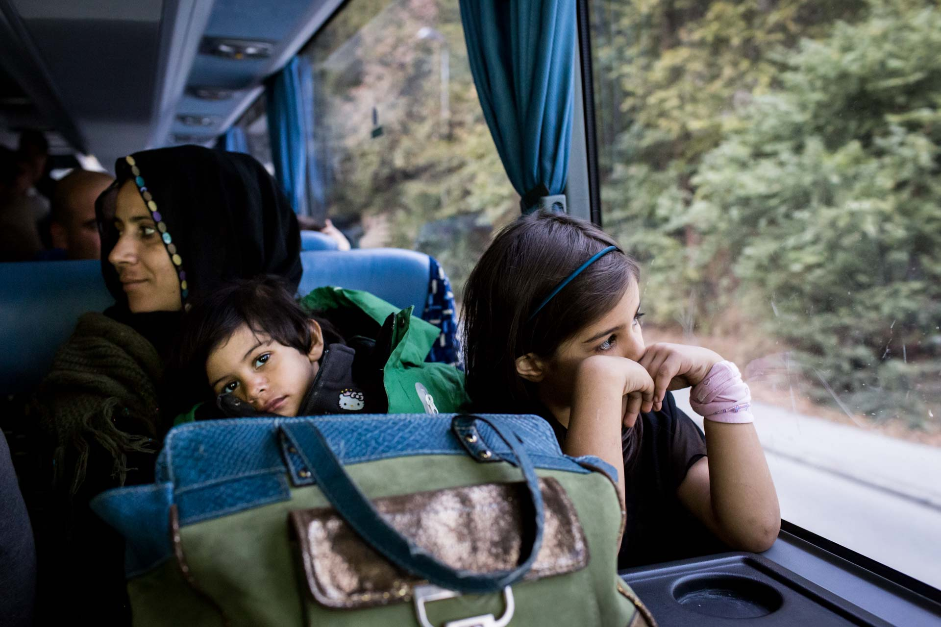 A family from Iraq sits in a bus of the German federal police in Passau, Germany, on their way to a processing center, where they will get a transport to an asylum center to apply for refugee status.