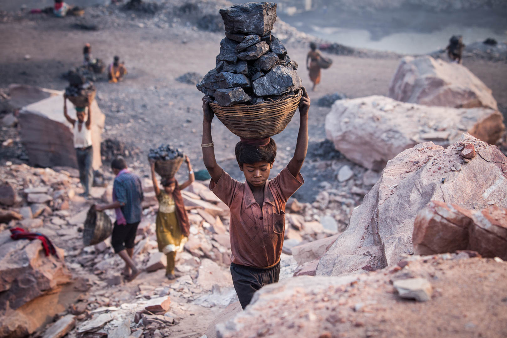 A small boy carries almost his own body-weight in coal on his head, after he collected the coal in a government-run mine near the city of Dhanbad. Some of the kids collecting the coal are as young as six years old.
