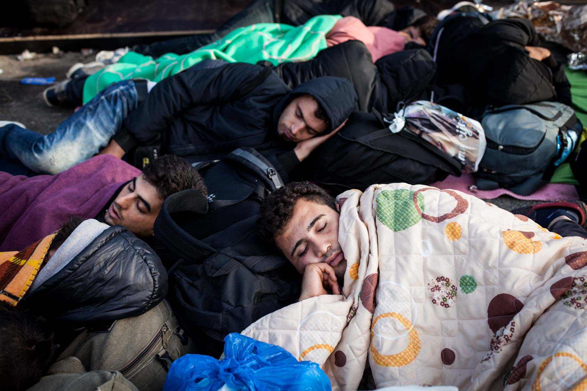 A group of young men sleeps beneath blankets on the closed border to Hungary.