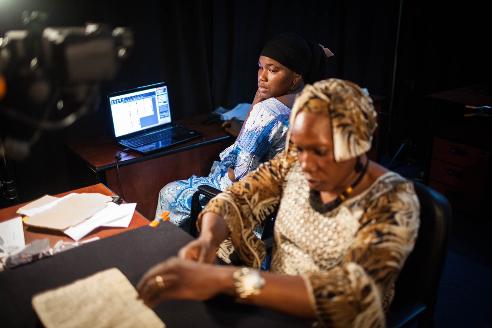 Two female restorers prepare a manuscript for archiving in a facility in Bamako.