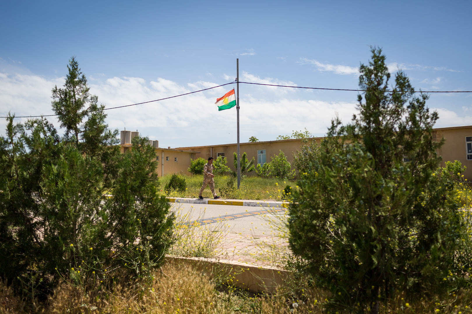 A Peshmerga soldier walks the perimeters of the Zerewani compound near Erbil, where coalition forces are training the Peshmerga, the armed forces of the Kurdish Autonomous Region of Iraq.