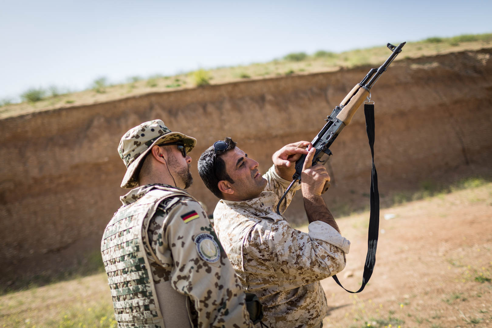 A German military adviser helps a Kurdish soldier checking the barrel of his AK-47.