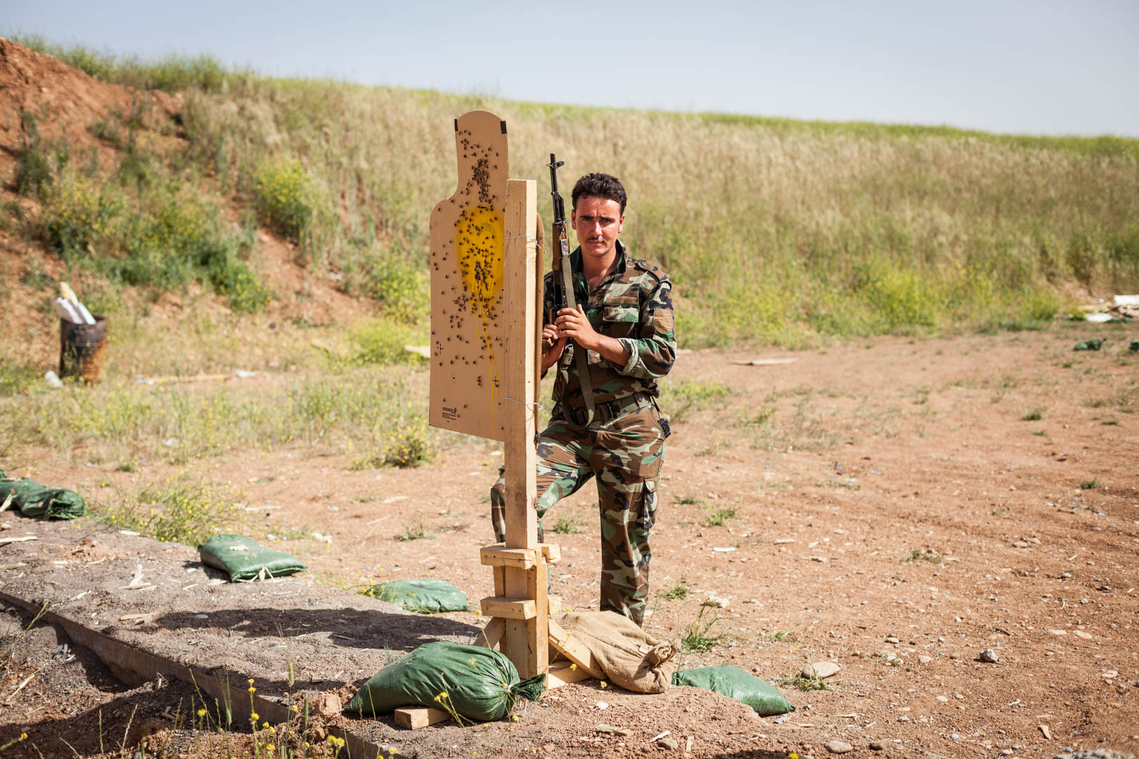 A member of the Peshmerga awaits his instructor at the shooting range.