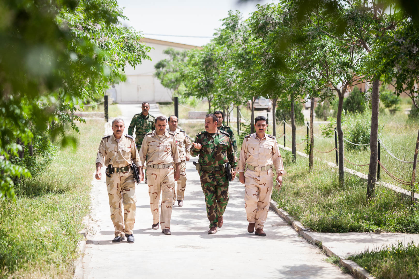 A group of Kurdish officers and officials is walking the Zerewani compound.
