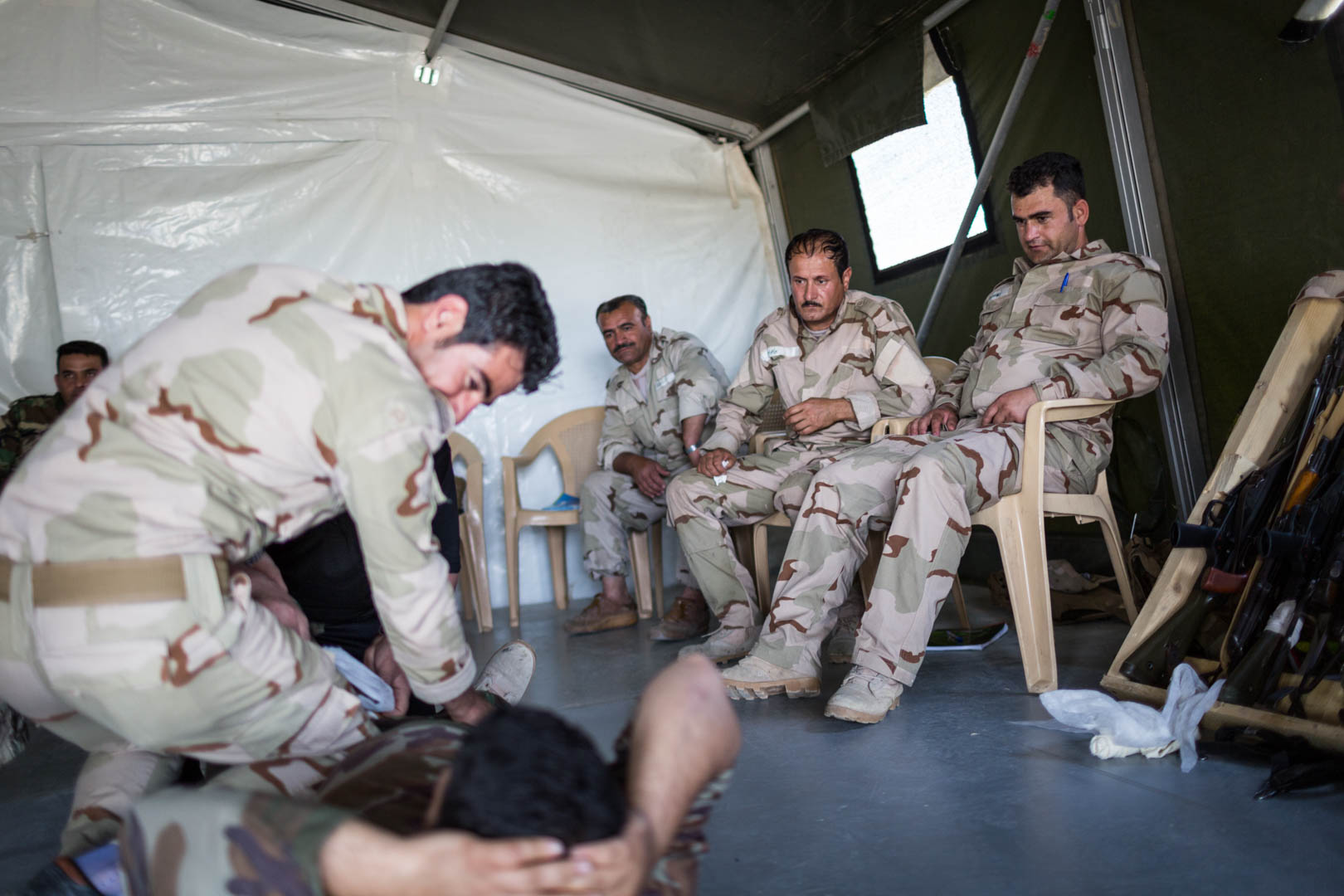 A group of Peshmerga officers is watching their soldiers take part in a training led by German forces to treat combat injuries.