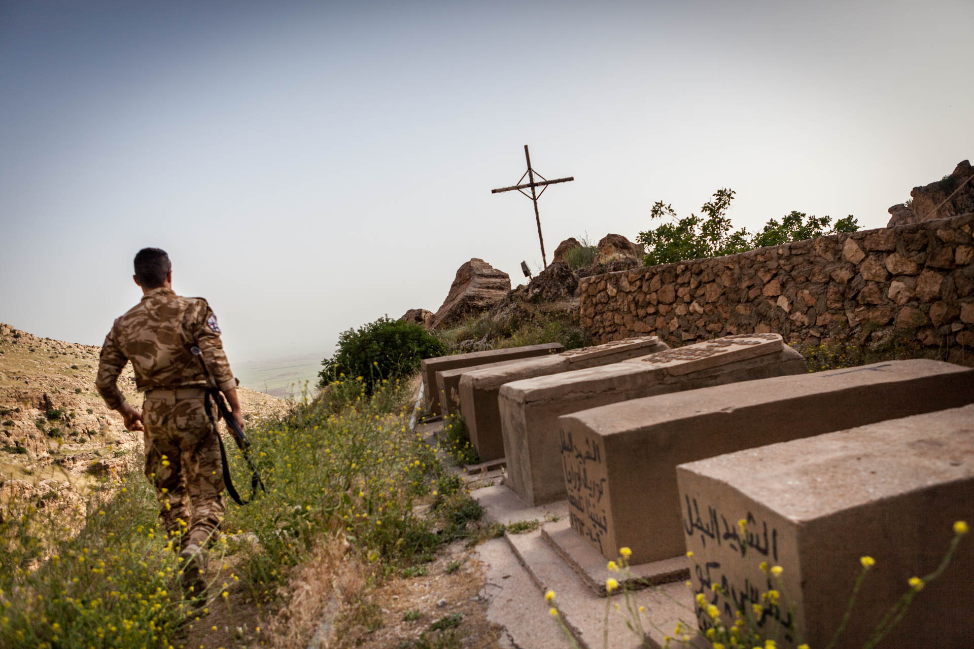 Sargon walks by graves that are situated in the compound of Rabban Hermizd monastery in the mountains behind Alqosh. Today, both Peshmerga and the Dwekh Nawsha are responsible for the security of the monastery.
