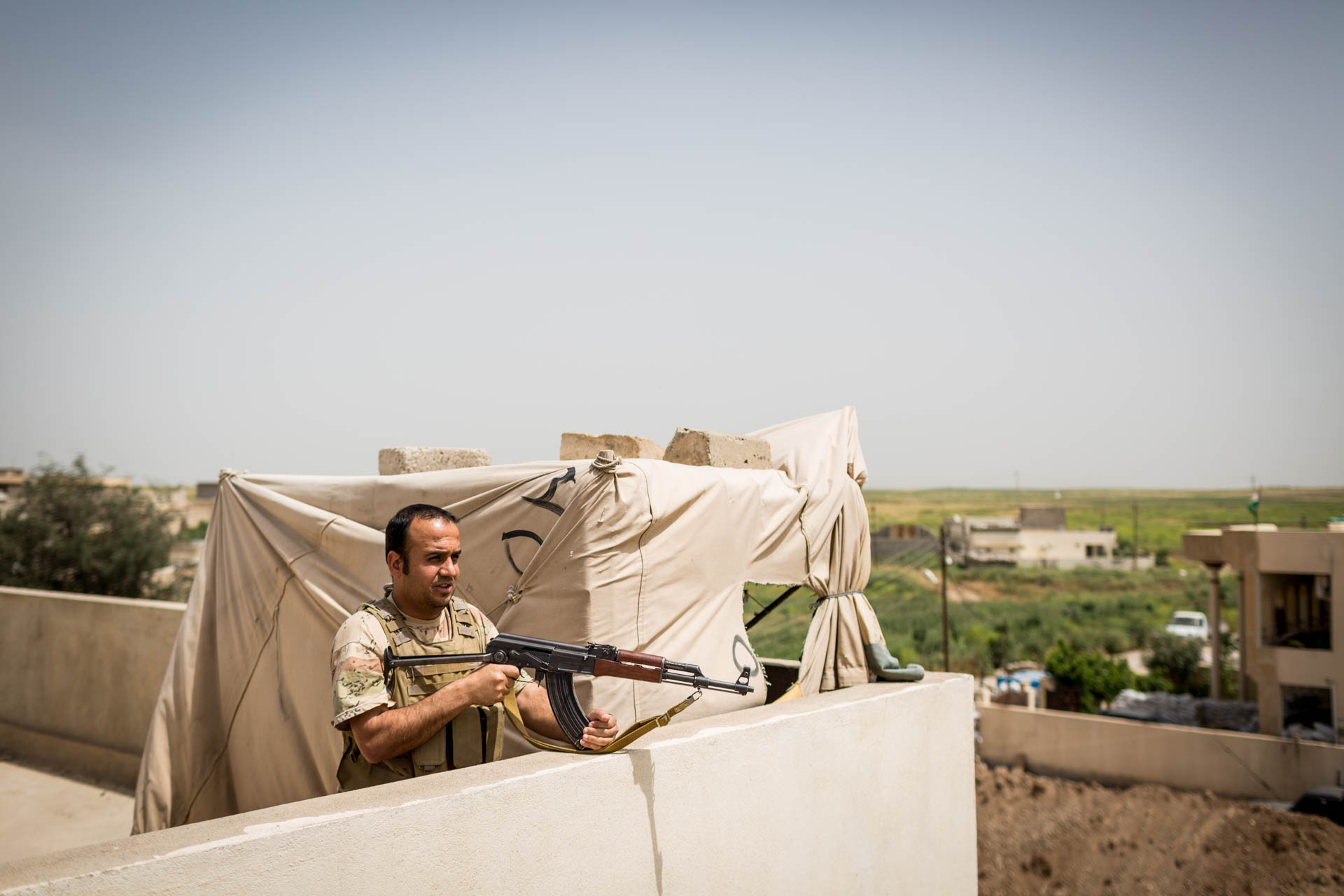 A member of the Dwekh Nawsha stands guard on a house in Bakufa. The next village down the road, Batnay, is in control of the Islamic State.