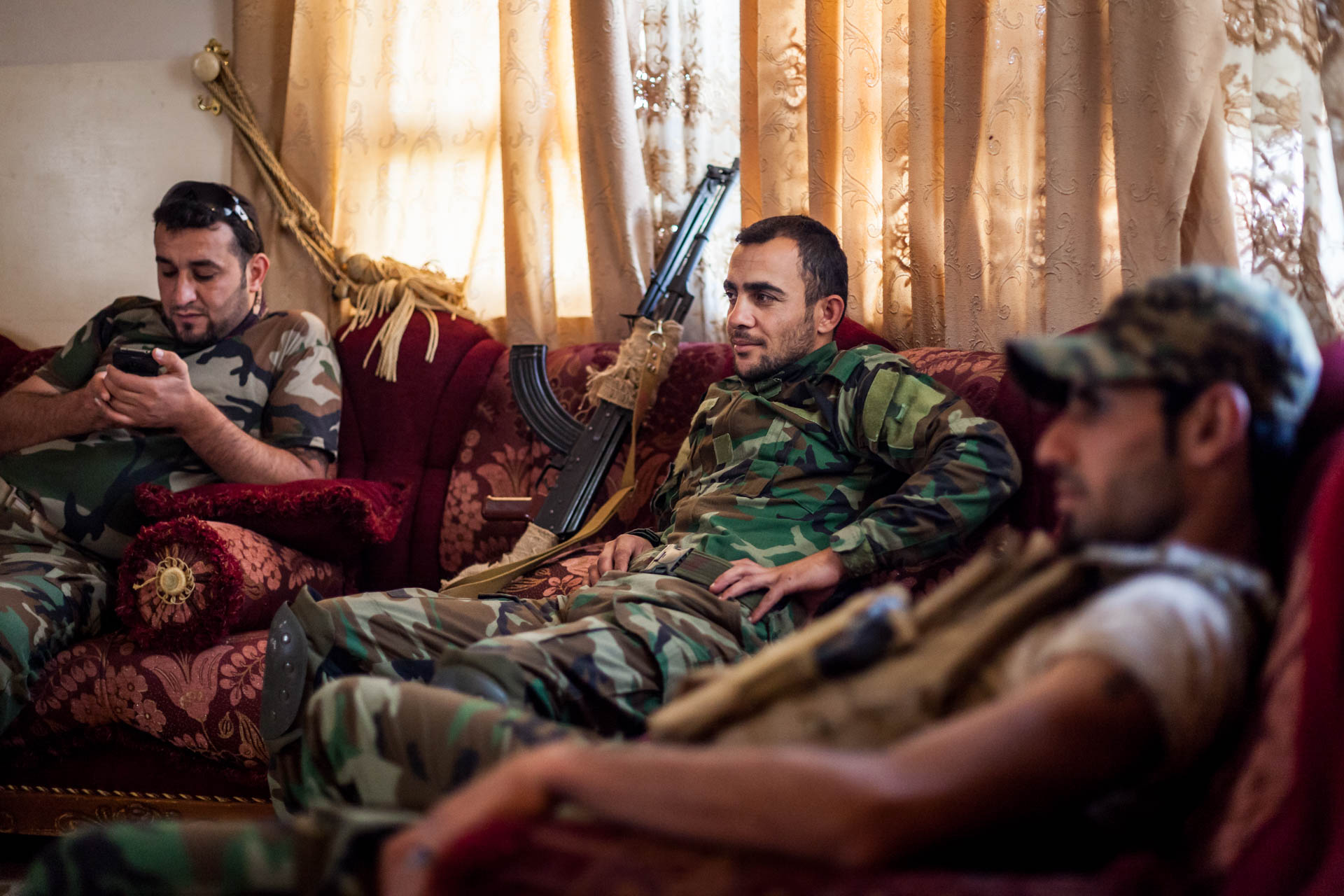 Three fighters of the Dwekh Nawsha in the living room of their headquarter in Bakufa. For most of the time, the Islamic State does not attact, but sometimes they shoot mortars or use the morning fog to attempt an advance.