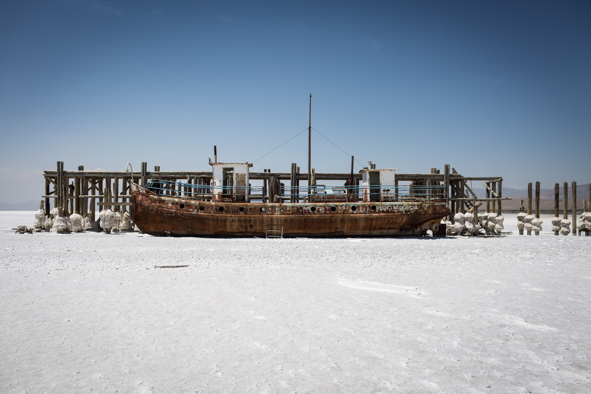 A ship sitting on salt rusts in the sun.