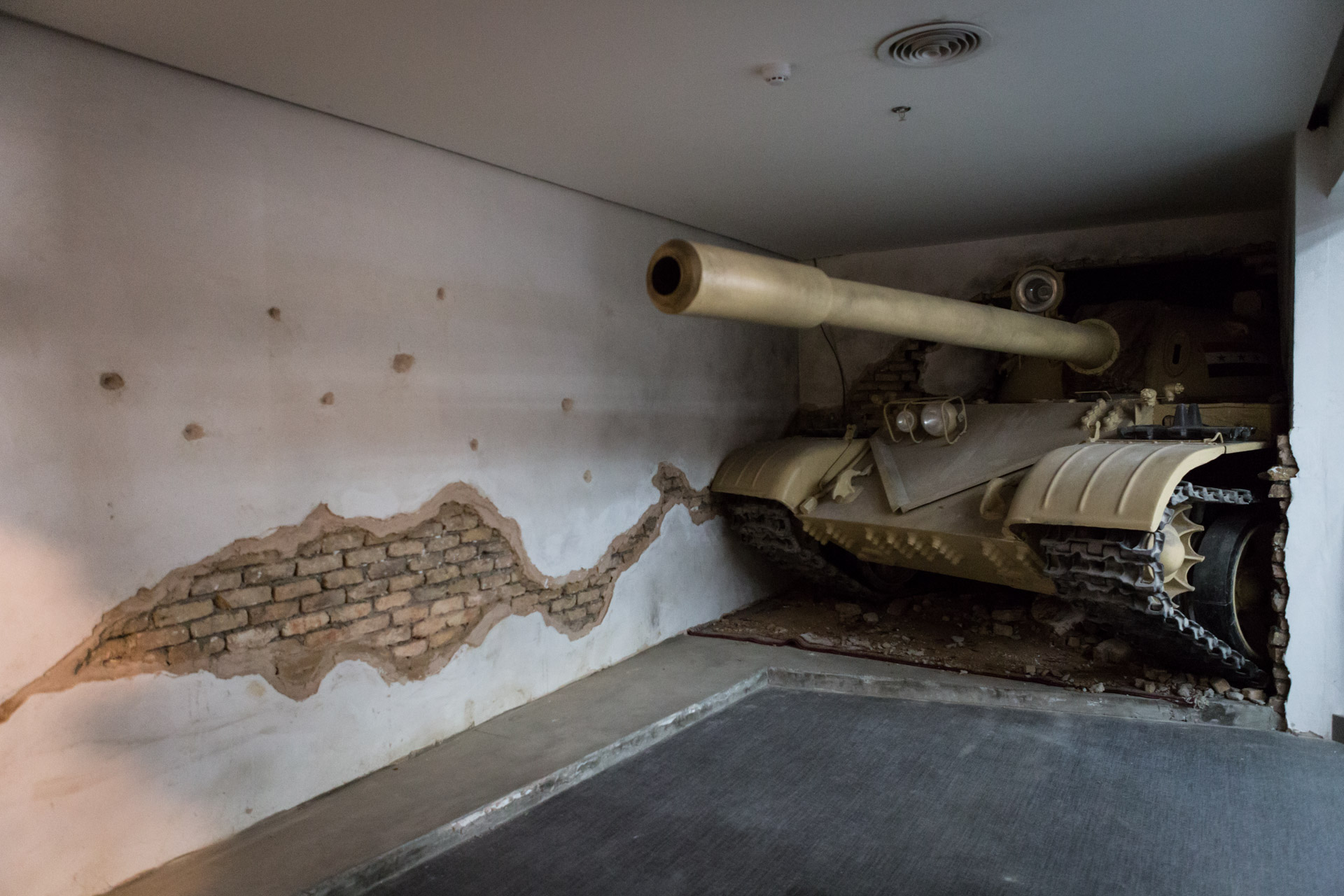The front of a tank is breaking through a wall.
