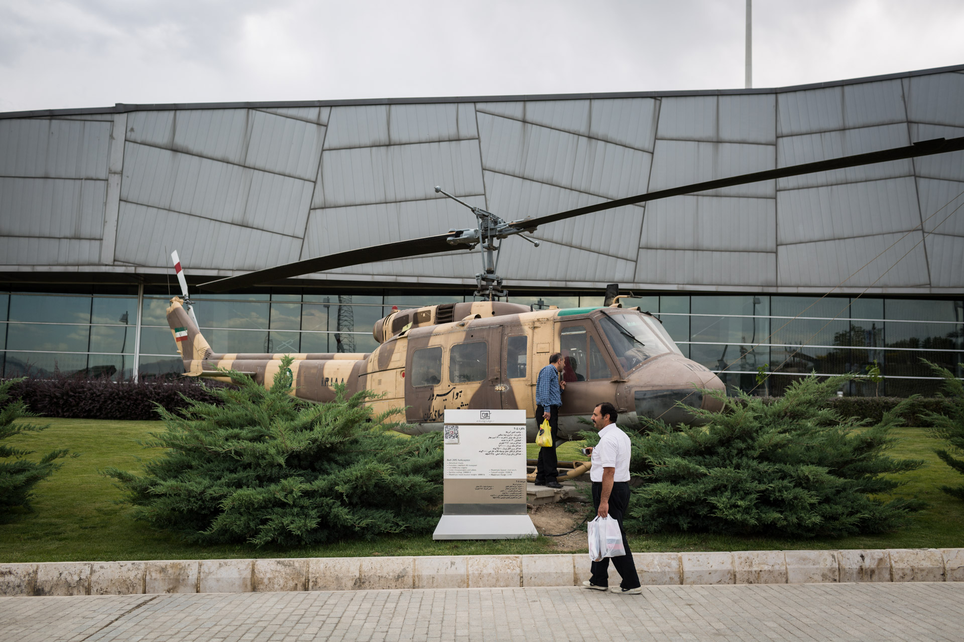 Two visitors of the museum inspect an Iranian helicopter, used in the Iran-Iraq war from 1980-1988.
