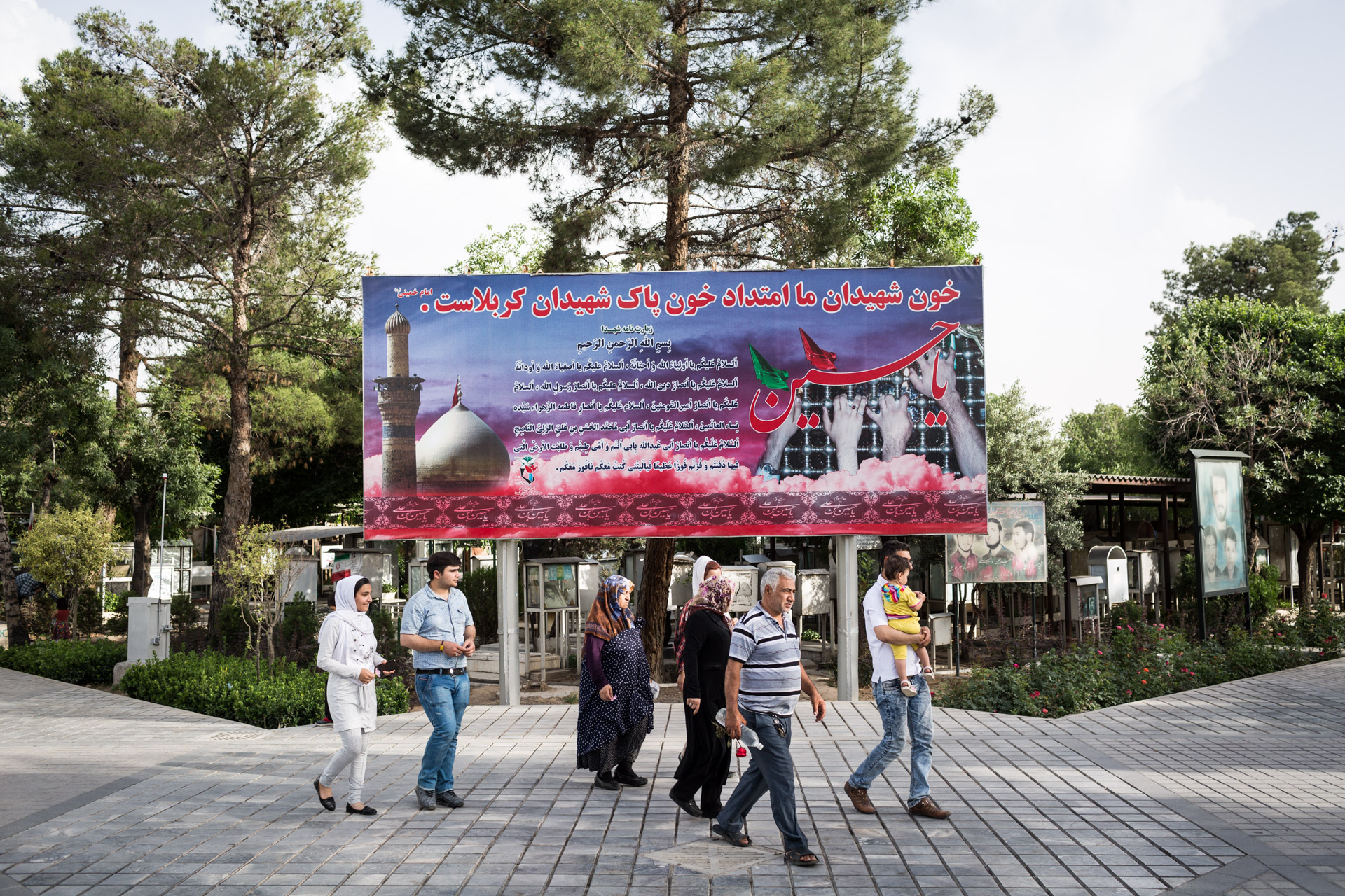 "A group of people walk in front of a billboard reminding of martyrs on Behesht-e Zahra (""the paradise of Zahra""), Iran's biggest cemetery."