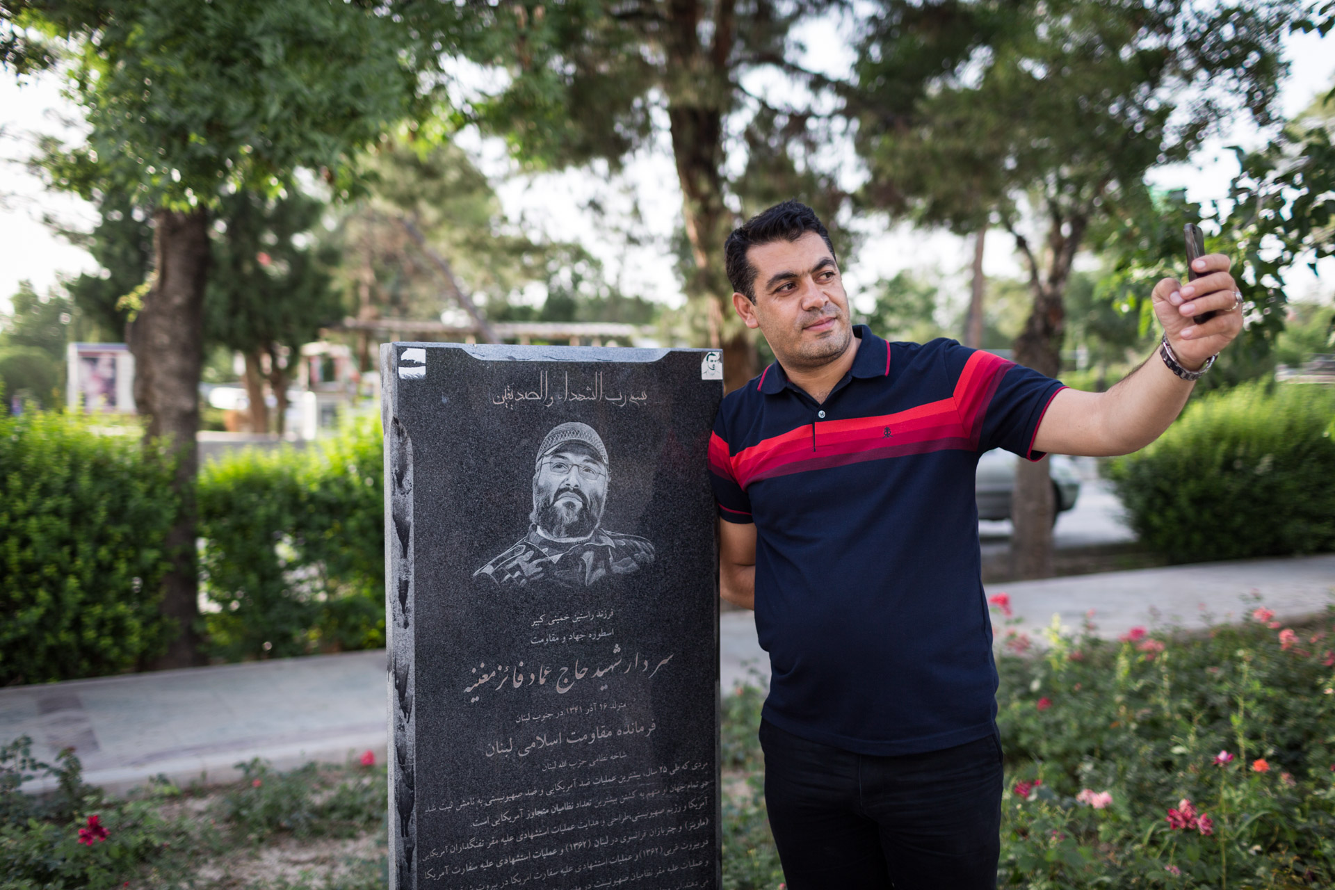 A visitor of the cemetery takes a selfie with a remembrance stele of Imad Mughniyeh, a member of Shia party Hezbollah, a close ally of Iran in Lebanon. Mughniyeh was assassinated in Syria and is considered a martyr.