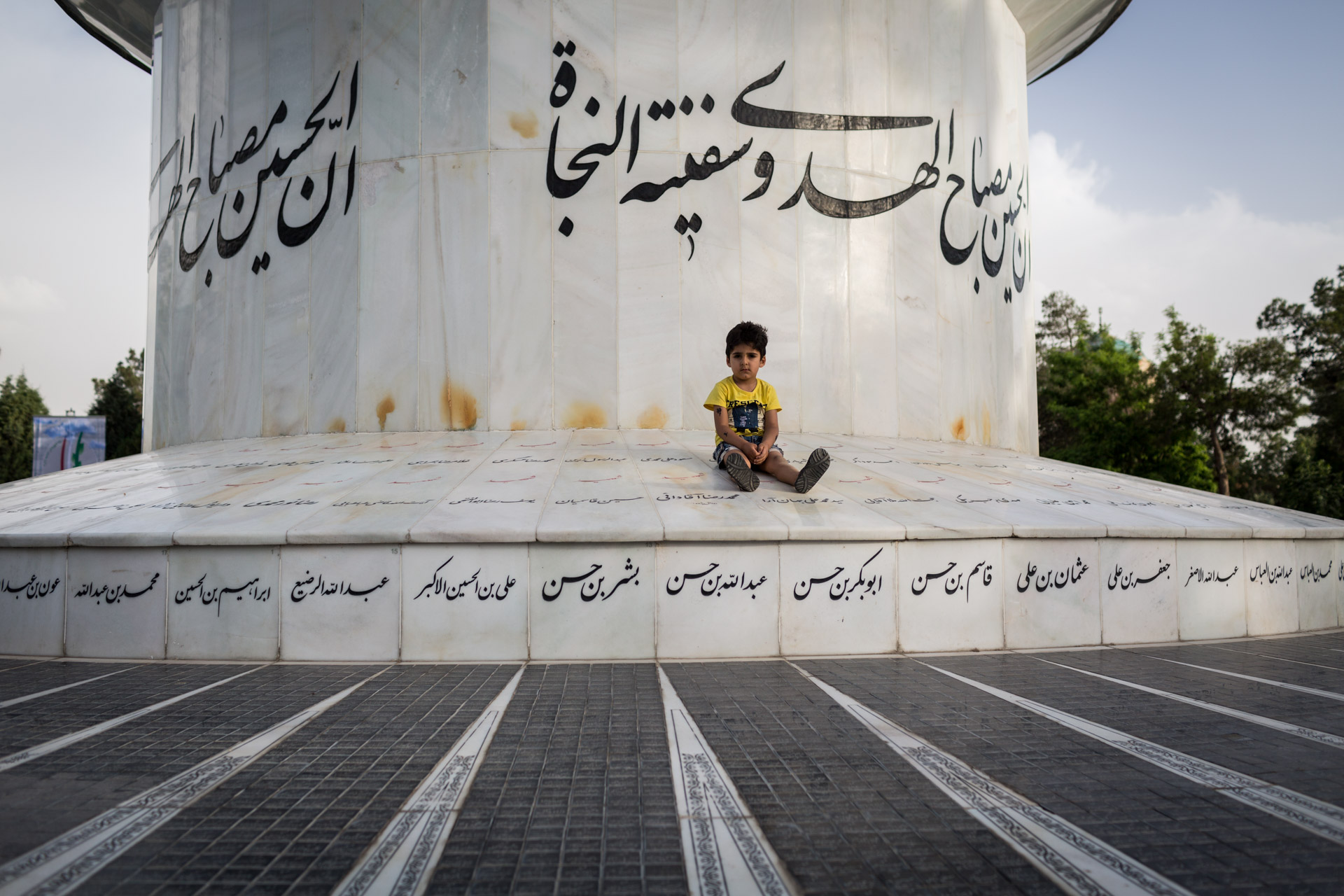 A boy sits on a memorial for members of the Iranian navy that have fallen in the war.