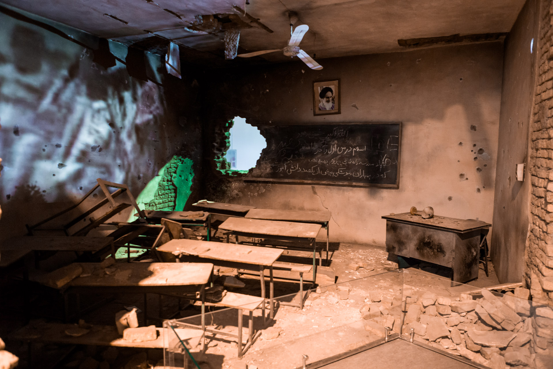 Devastated by Iraqi bombs, an old Iranian classroom has been set up, including a video projection on the left wall.